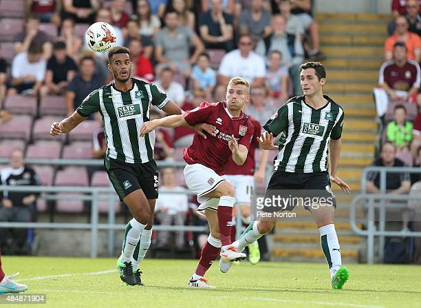Alfie Potter of Northampton Town challenges for the ball with Curtis Nelson and Carl McHugh of Plymouth Argyle during the Sky Bet League Two match...