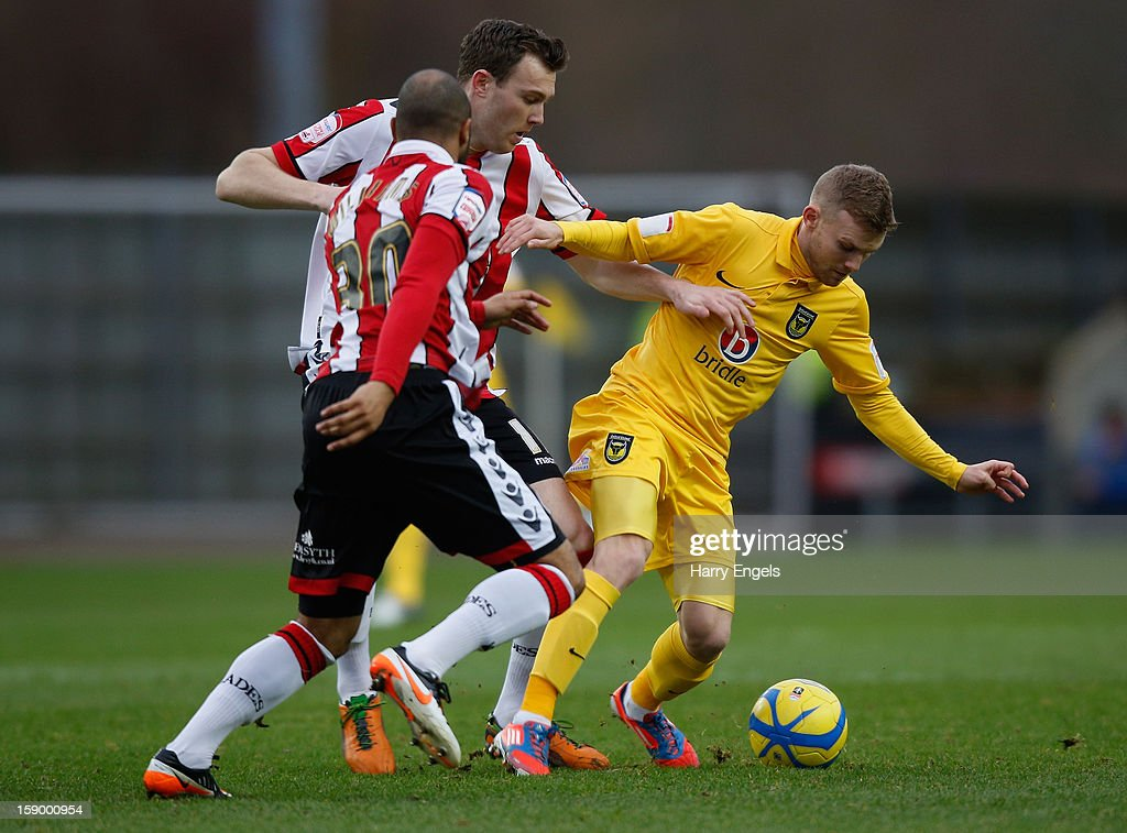 Alfie Potter of Oxford United competes for the ball with Kevin McDonald and Marcus Williams of Sheffield United during the FA Cup Third Round match between Oxford United and Sheffield United at the Kassam Stadium on January 5, 2013 in Oxford, England.