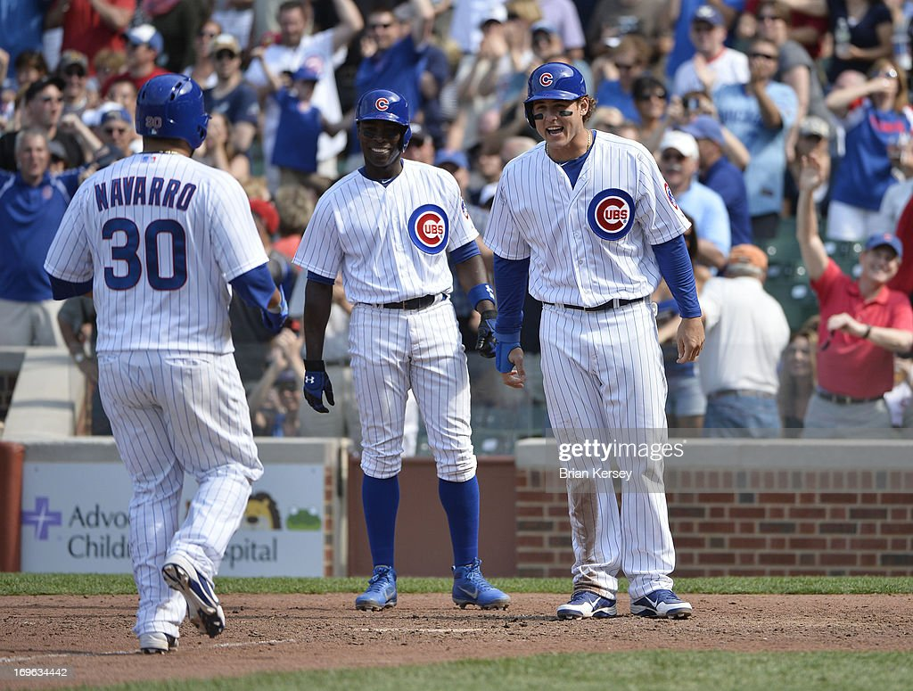 <a gi-track='captionPersonalityLinkClicked' href=/galleries/search?phrase=Alfonso+Soriano&family=editorial&specificpeople=202251 ng-click='$event.stopPropagation()'>Alfonso Soriano</a> #12 of the Chicago Cubs (C) and <a gi-track='captionPersonalityLinkClicked' href=/galleries/search?phrase=Anthony+Rizzo&family=editorial&specificpeople=7551494 ng-click='$event.stopPropagation()'>Anthony Rizzo</a> #44 wait for <a gi-track='captionPersonalityLinkClicked' href=/galleries/search?phrase=Dioner+Navarro&family=editorial&specificpeople=593062 ng-click='$event.stopPropagation()'>Dioner Navarro</a> #30 at home plate after Navarro hit a three-run home run scoring Soriano and Rizzon during the seventh inning at Wrigley Field on May 29, 2013 in Chicago, Illinois.