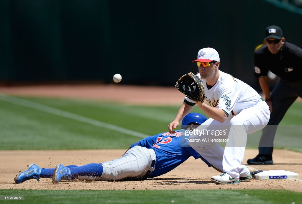Alfonso Soriano #12 of the Chicago Cubs dives back into first base safe as Nate Freiman #7 of the Oakland Athletics takes the throw at O.co Coliseum on July 4, 2013 in Oakland, California.