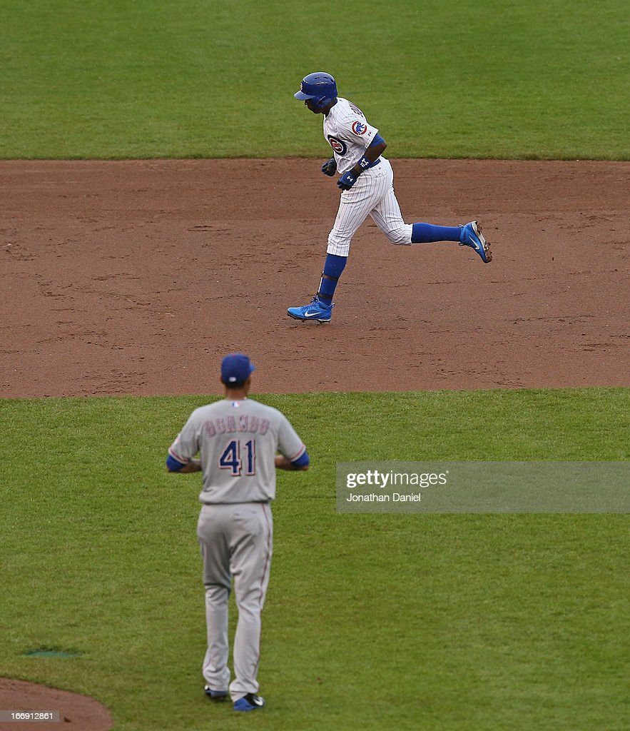 <a gi-track='captionPersonalityLinkClicked' href=/galleries/search?phrase=Alfonso+Soriano&family=editorial&specificpeople=202251 ng-click='$event.stopPropagation()'>Alfonso Soriano</a> #12 of the Chicago Cubs is watched by <a gi-track='captionPersonalityLinkClicked' href=/galleries/search?phrase=Alexi+Ogando&family=editorial&specificpeople=6889214 ng-click='$event.stopPropagation()'>Alexi Ogando</a> #41 of the Texas Rangers as he runs the bases after hitting a solo home run in the 3rd inning at Wrigley Field on April 18, 2013 in Chicago, Illinois.