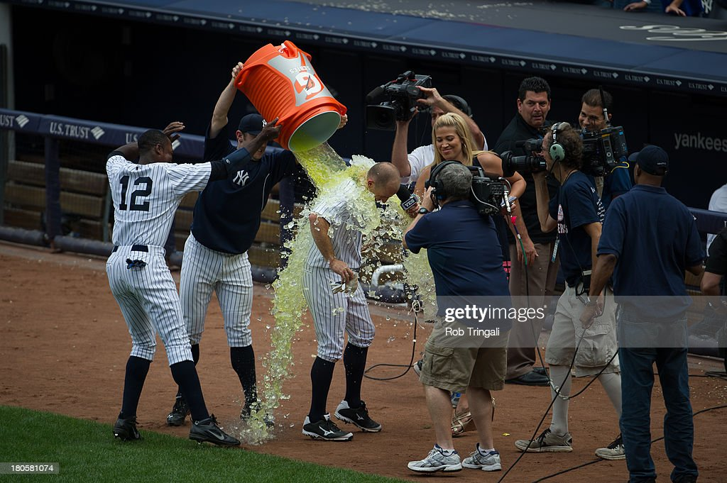 Alfonso Soriano #12 of the New York Yankees and David Robertson #30 throw gatorade on Brett Gardner #11 after he hits a game winning home run against the Detroit Tigers at Yankee Stadium on August 11, 2013 in the Bronx borough of Manhattan.
