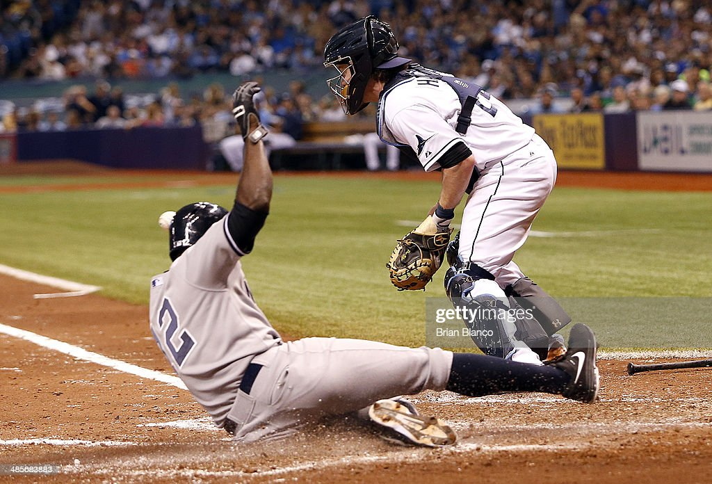 Alfonso Soriano #12 of the New York Yankees beats the throw home to catcher Ryan Hanigan #24 of the Tampa Bay Rays to score off of Kelly Johnson's double during the fifth inning of a game on April 19, 2014 at Tropicana Field in St. Petersburg, Florida.
