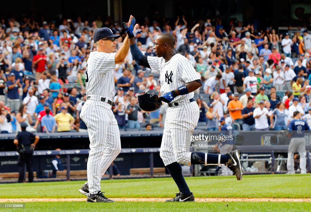 Alfonso Soriano #12 of the New York Yankees celebrates his ninth inning game winning base hit against the Tampa Bay Rays with manager Joe Girardi #28 at Yankee Stadium on July 28, 2013 in the Bronx borough of New York City.