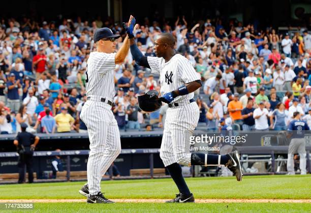Alfonso Soriano of the New York Yankees celebrates his ninth inning game winning base hit against the Tampa Bay Rays with manager Joe Girardi at...