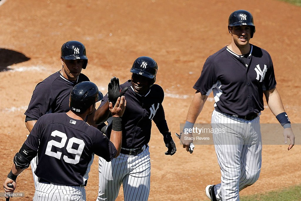 Alfonso Soriano #12 of the New York Yankees is congratulated by teammates following a home run in the fourth inning of a game against the Boston Red Sox at George M. Steinbrenner Field on March 18, 2014 in Tampa, Florida.