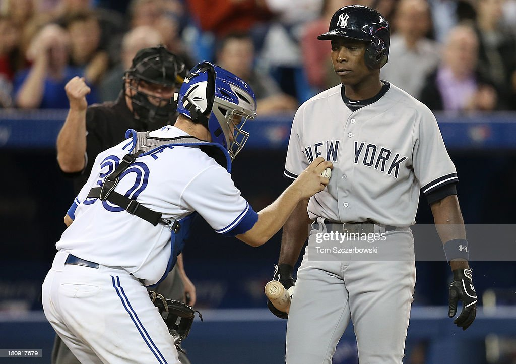 <a gi-track='captionPersonalityLinkClicked' href=/galleries/search?phrase=Alfonso+Soriano&family=editorial&specificpeople=202251 ng-click='$event.stopPropagation()'>Alfonso Soriano</a> #12 of the New York Yankees is tagged out in the sixth inning after striking out by <a gi-track='captionPersonalityLinkClicked' href=/galleries/search?phrase=Josh+Thole&family=editorial&specificpeople=5741573 ng-click='$event.stopPropagation()'>Josh Thole</a> #30 of the Toronto Blue Jays as home plate umpire Gerry Davis #12 signals with an out call on September 17, 2013 at Rogers Centre in Toronto, Ontario, Canada.