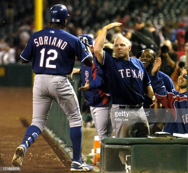 Alfonso Soriano of the Texas Rangers is greeted by Kevin Mench after hitting a leadoff solo home run in the 12th inning of 32 victory over the Los...