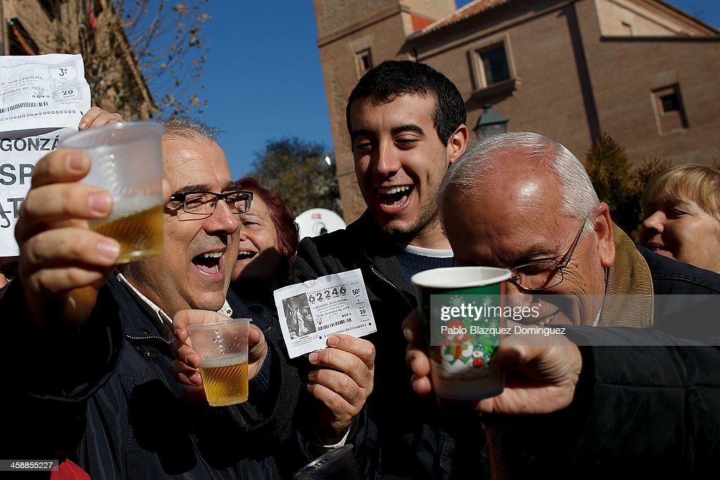 Alfonso (L), who has been unemployed for eight months celebrates with his son Diego (C) and friends after he won a top prize ticket number in Spain's Christmas lottery, 'El Gordo' (Fat One) on December 22, 2013 in Leganes, near Madrid, Spain. This year's winning number is 62246, with a total of 4 million euros for the top prize to be shared between ten ticket holders. The total prize fund is worth 2.5bn.