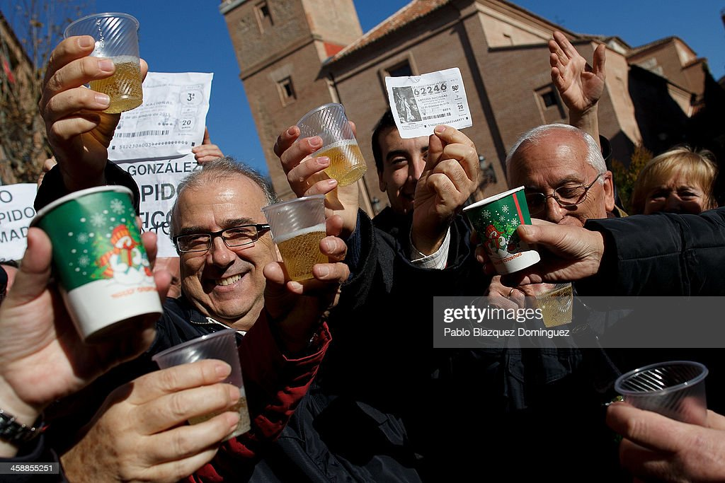 Alfonso (L), who has been unemployed for eight months, celebrates with his son Diego (C) and friends after he won a top prize ticket number in Spain's Christmas lottery, 'El Gordo' (Fat One) on December 22, 2013 in Leganes, near Madrid, Spain. This year's winning number is 62246, with a total of 4 million euros for the top prize to be shared between ten ticket holders. The total prize fund is worth 2.5bn.