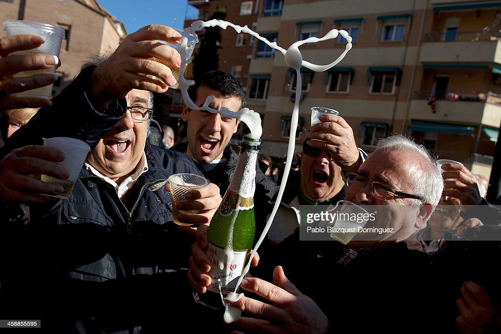 Alfonso (L), who has been unemployed for eight months, celebrates with his son Diego (2nd L) and friends after he won a top prize ticket number in Spain's Christmas lottery, 'El Gordo' (Fat One) on December 22, 2013 in Leganes, near Madrid, Spain. This year's winning number is 62246, with a total of 4 million euros for the top prize to be shared between ten ticket holders. The total prize fund is worth 2.5bn.