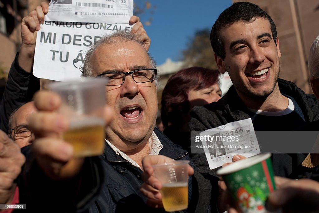 Alfonso (L), who has been unemployed for eight months, celebrates with his son Diego (R) and friends after he won a top prize ticket number in Spain's Christmas lottery, 'El Gordo' (Fat One) on December 22, 2013 in Leganes, near Madrid, Spain. This year's winning number is 62246, with a total of 4 million euros for the top prize to be shared between ten ticket holders. The total prize fund is worth 2.5bn.