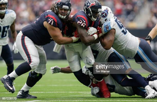 Alfred Blue of the Houston Texans is tackled by Jayon Brown of the Tennessee Titans Wesley Woodyard and Daquan Jones in the fourth quarter at NRG...