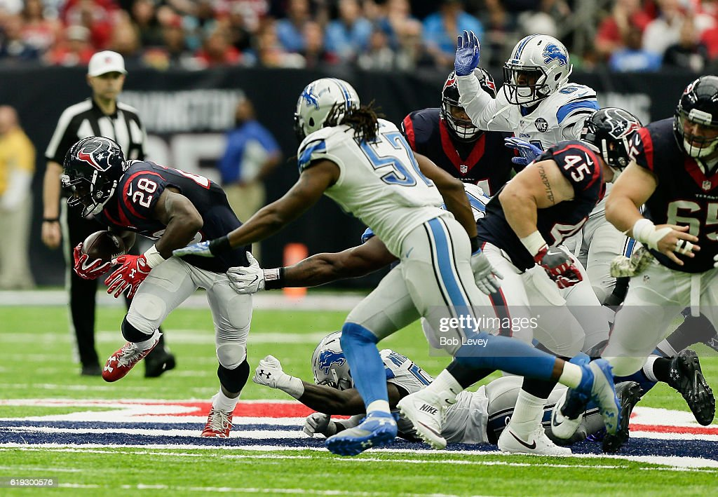 Alfred Blue #28 of the Houston Texans rushes past Josh Bynes #57 of the Detroit Lions at NRG Stadium on October 30, 2016 in Houston, Texas.