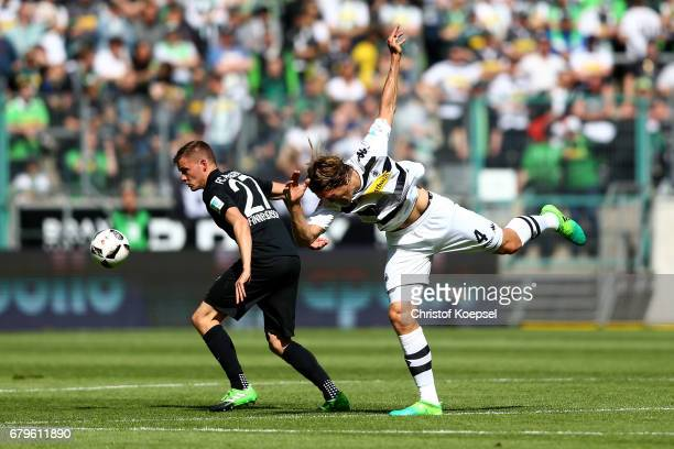 Alfred Finnbogason of Augsburg and Jannik Vestergaard of Moenchengladbach go up for a header during the Bundesliga match between Borussia...