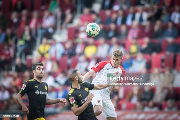 Alfred Finnbogason of Augsburg and Oemer Toprak of Borussia Dortmund compete for the ball during the Bundesliga match between FC Augsburg and...