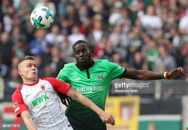 Alfred Finnbogason of Augsburg and Salif Sane of Hannover fight for the ball during the Bundesliga match between FC Augsburg and Hannover 96 at...