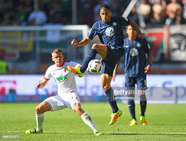 Alfred Finnbogason of FC Augsburg challenges Ricardo Rodriguez of VfL Wolfsburg during the Bundesliga match between FC Augsburg and VfL Wolfsburg at...