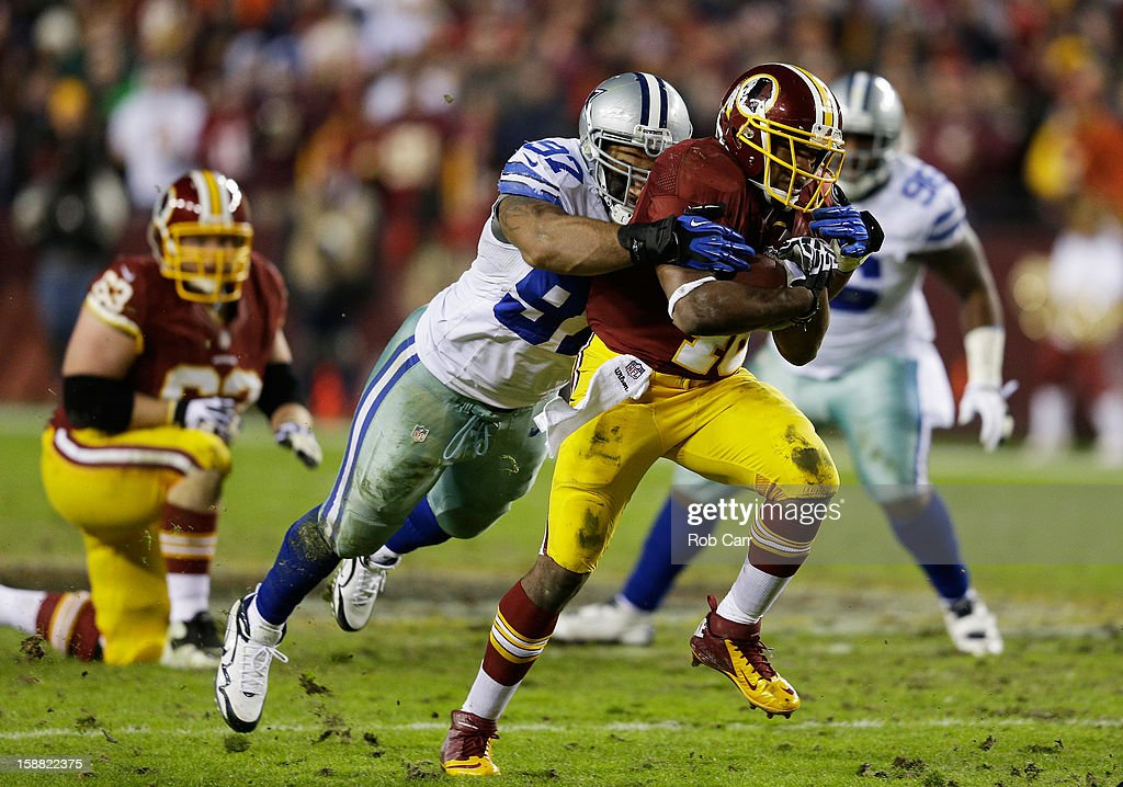 Alfred Morris #46 of the Washington Redskins is tackled by Jason Hatcher #97 of the Dallas Cowboys in the second quarter of their game at FedExField on December 30, 2012 in Landover, Maryland.