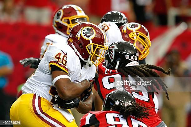 Alfred Morris of the Washington Redskins rushes against Adrian Clayborn of the Atlanta Falcons at Georgia Dome on October 11 2015 in Atlanta Georgia