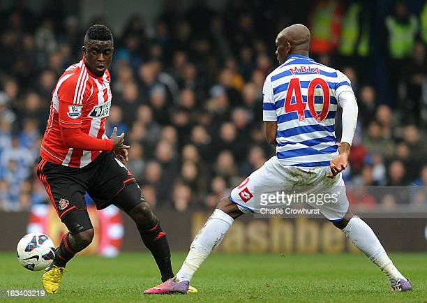 Alfred N'Diaye of Sunderland goes past Stephane Mbia of Queens Park Rangers during the Barclays Premier League match between Queens Park Rangers and...
