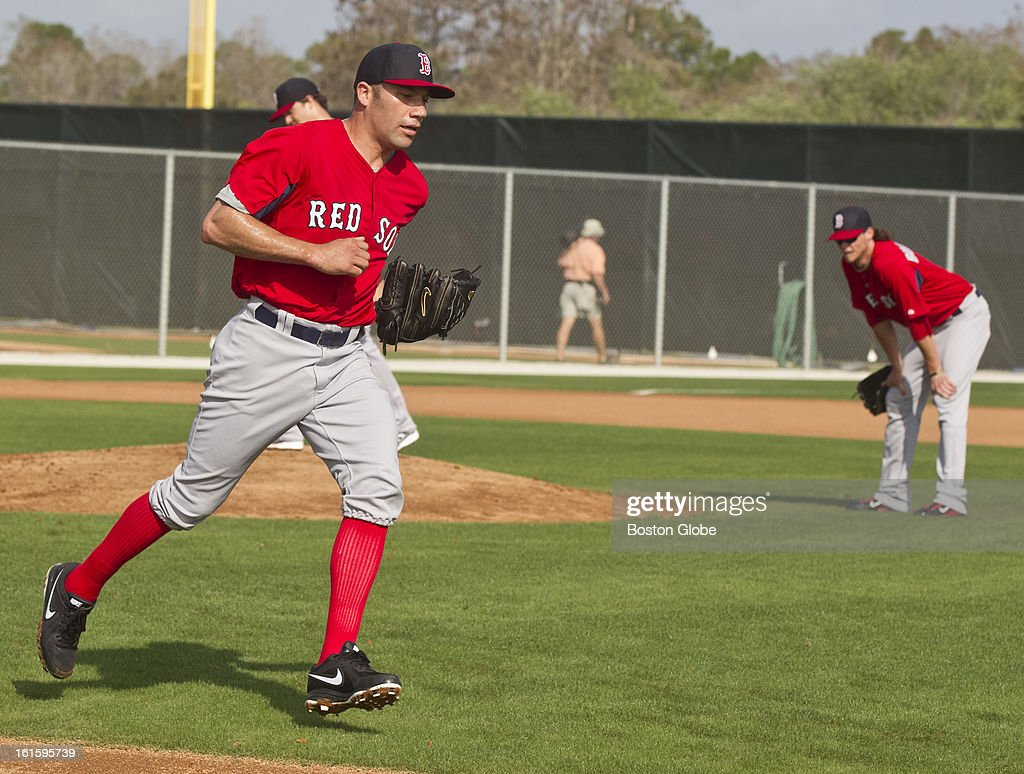 Alfredo Aceves covers first base during a drill as Clay Buchholz watches with his hands on his knees during first official spring training day for the Boston Red Sox pitchers and catchers at JetBlue Park on Tuesday, Feb. 12, 2013. Buchholz left the field during this drill with a strained hamstring.
