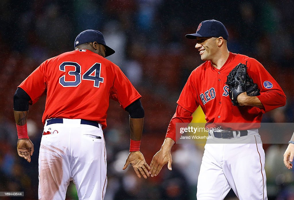 Alfredo Aceves #91 of the Boston Red Sox is congratulated by teammate David Ortiz #34 after closing out the game against the Cleveland Indians during the game on May 24, 2013 at Fenway Park in Boston, Massachusetts.