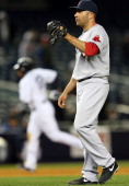 Alfredo Aceves of the Boston Red Sox reacts after giving up a three run home run in the eighth inning as Vernon Wells of the New York Yankees rounds...