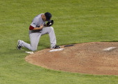 Alfredo Aceves of the Boston Red Sox takes a knee before pitching against the Texas Rangers at Rangers Ballpark in Arlington on July 24 2012 in...