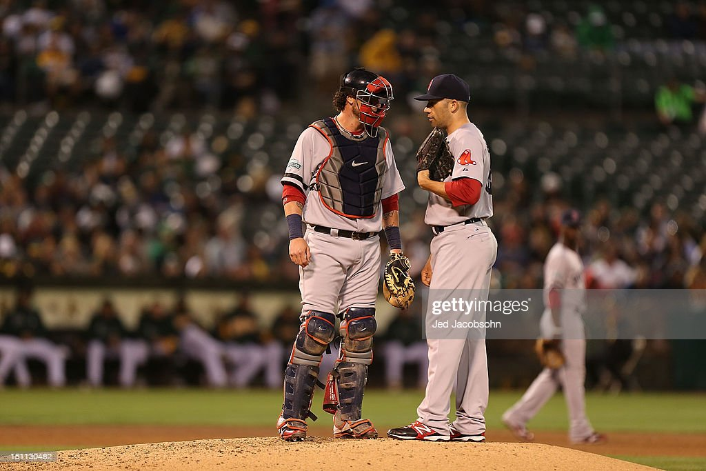<a gi-track='captionPersonalityLinkClicked' href=/galleries/search?phrase=Alfredo+Aceves&family=editorial&specificpeople=5514493 ng-click='$event.stopPropagation()'>Alfredo Aceves</a> #61 of the Boston Red Sox talks with <a gi-track='captionPersonalityLinkClicked' href=/galleries/search?phrase=Jarrod+Saltalamacchia&family=editorial&specificpeople=836404 ng-click='$event.stopPropagation()'>Jarrod Saltalamacchia</a> #39 against the Oakland Athletics during a Major League Baseball game at the O.co Coliseum on September 1, 2012 in Oakland, California.