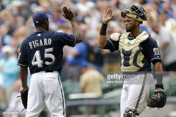 Alfredo Figaro of the Milwaukee Brewers celebrates with Martin Maldonado after the 92 win over the Washington Nationals at Miller Park on June 25...