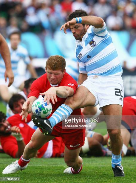 Alfredo Lalanne of Argentina kicks as Bidzina Samkharadze of Georgia dives for the ball during the IRB 2011 Rugby World Cup Pool B match between...