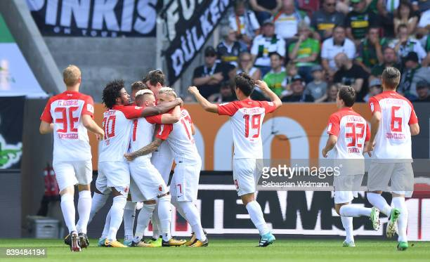 Alfreo Finnbogason of Augsburg celebrates with team mates during the Bundesliga match between FC Augsburg and Borussia Moenchengladbach at WWKArena...