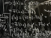 Close up image depicting complex mathematical equations and algebra written in chalk on a blackboard at school. Room for copy space.
