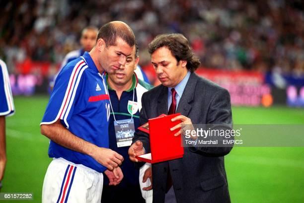 Algeria Coach Rabah Madjer presents a souvenir to France's Zinedine Zidane a Frenchman of Algerian parentage