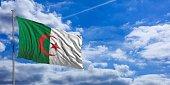 Algeria flag waving on a blue sky background. 3d illustration