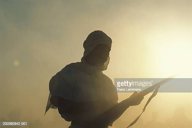 Algeria, Gourara Valley, silhouette of man with rifle, sunset