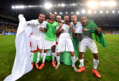 Algeria players celebrate qualifying for the knock out stage after the 11 draw in the 2014 FIFA World Cup Brazil Group H match between Algeria and...