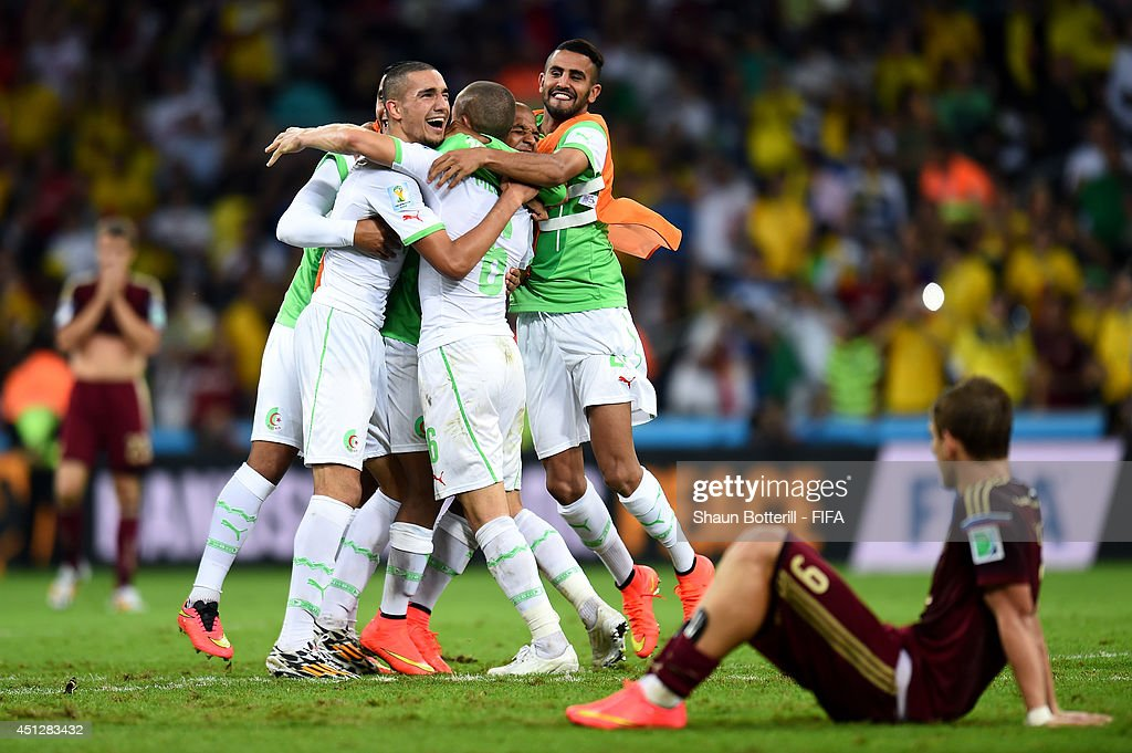 Algeria players celebrate qualifying for the knock out stage while Alexander Kokorin of Russia show his dejection after the 1-1 draw in the 2014 FIFA World Cup Brazil Group H match between Algeria and Russia at Arena da Baixada on June 26, 2014 in Curitiba, Brazil.