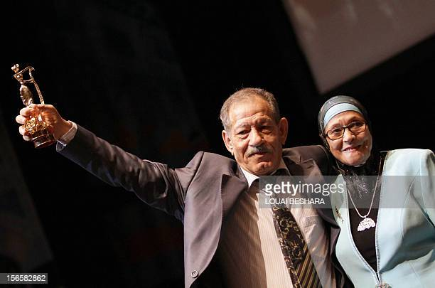 Algerian acters Shadia Abu Thraa and Algerian Ahmad bin Issa take the Golden Award for their movie 'Kharejun ann alQanon' during the final day of the...