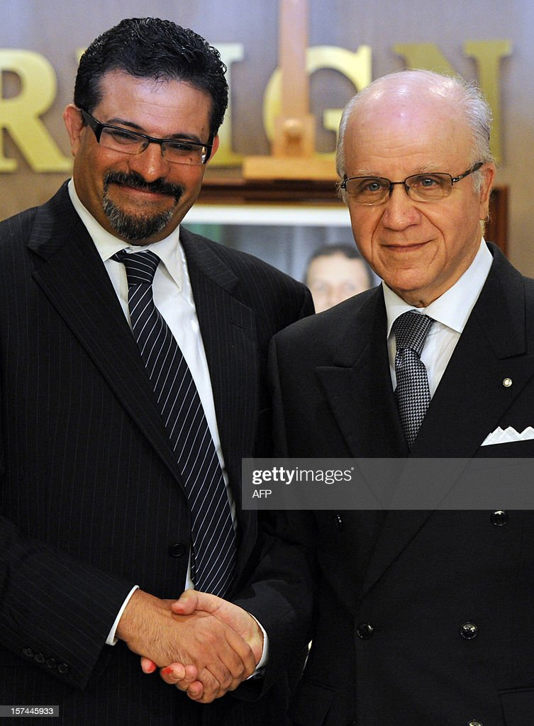Algerian Foreign Minister Mourad Medelci (R) shakes hands with his Tunisian counterpart Rafik Abdessalem at the Ministry of Foreign Affairs in Algiers on December 3, 2012.