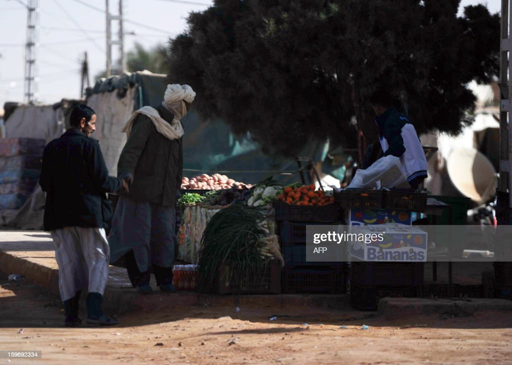 Algerian men sell fruits and vegetables in In Amenas, deep in the Sahara near the Libyan border, on January 18, 2013. Islamist hostage-takers at a nearby gas field in the area, more than 1,300 kms southeast of the capital Algiers, demanded a prisoner swap and an end to the French military campaign in Mali, a report said, while 30 foreigners were reported still missing in the worst international hostage drama for years.