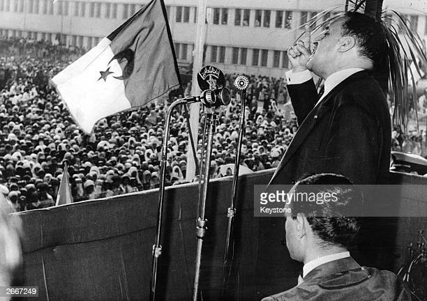 Algerian nationalist leader Ferhat Abbas speaking at a public meeting in Casablanca beside King Hassan II of Morocco