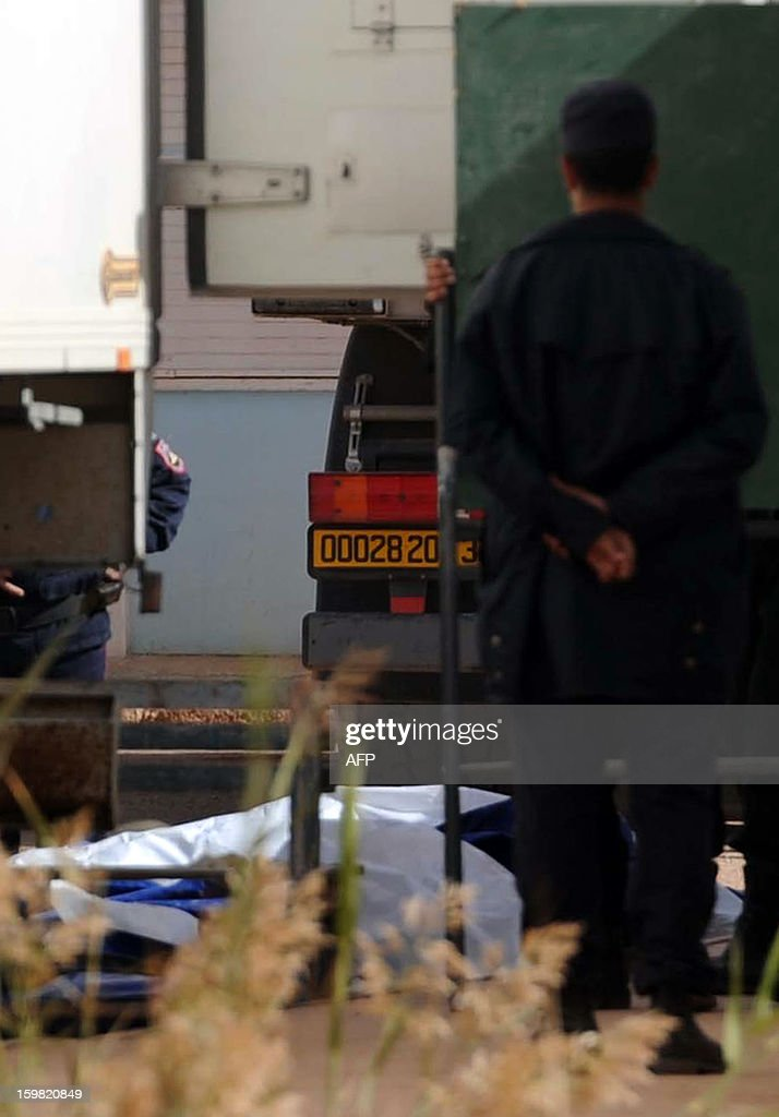 Algerian police keep guard as body bags of victims that were killed during the hostage crisis at a desert gas plant in Algeria's deep south are unloaded from a refrigerated truck in In Amenas that is transporting the bodies to hospital for identification on January 21, 2012. Two days after Algerian forces ended a hostage crisis at a desert gas plant, the exact toll of those killed in the bloodbath remained unknown, amid fears the total number of hostages who died could reach 50.