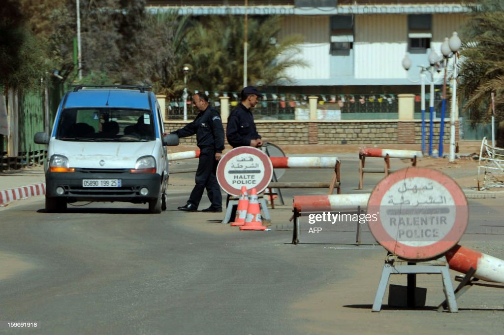 Algerian policemen stop cars at a checkpoint in In Amenas deep in the Sahara near the Libyan border on January 18 2013 as Islamist hostagetakers at a...