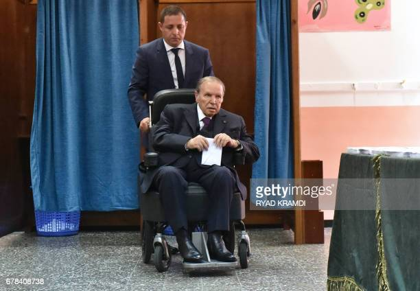 Algerian President Abdelaziz Bouteflika is seen on a wheelchair as he votes at a polling station in Algiers on May 4 2017 Algerians voted for a new...