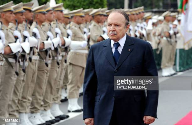 Algerian President Abdelaziz Bouteflika reviews a guard of honour during his visit to the commemorative stele outside the seaport in Algiers on May 2...