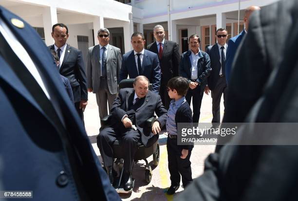 Algerian President Abdelaziz Bouteflika talks to his nephew after casting his vote at a polling station in Algiers on May 4 2017 during parliamentary...