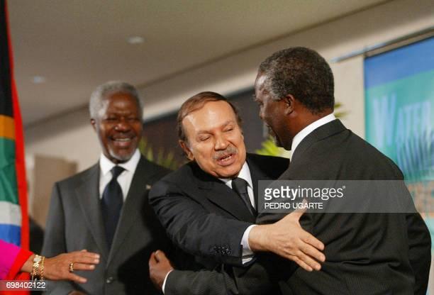 Algerian President Abdelaziz Bouteflika tries to reach Zanele Mbeki's hand while he hugs her husband South African President Thabo Mbeki as United...
