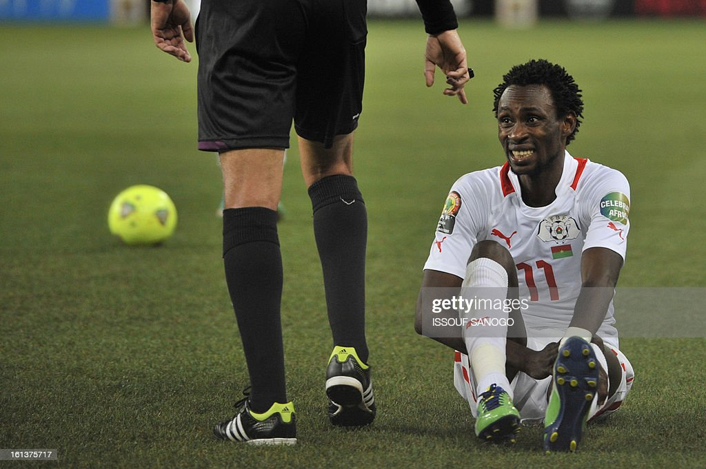 Algerian referee Djamel Haimoudi talks to Burkina Faso's midfielder Jonathan Pitroipa holding his knee while sitting on the pitch during the 2013 African Cup of Nations final football match between Burkina Faso and Nigeria on February 10, 2013 at Soccer City stadium in Johannesburg.